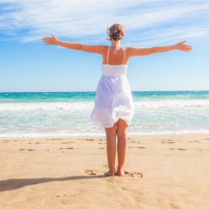 Frau steht am Strand