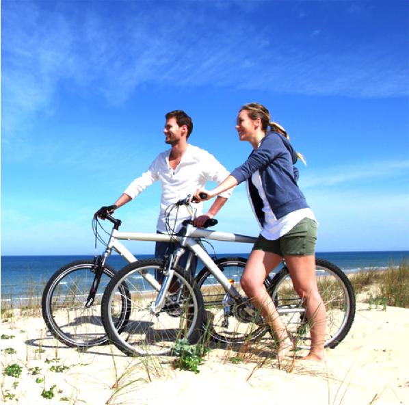 Paar fährt Fahrrad am Strand